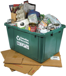 Photo of full green recycling bin on top of collapsed cardboard boxes