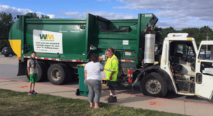 Photo of people talking outside garbage truck